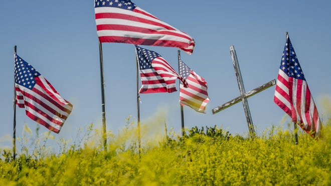 Flowers bloom in a Fort Peck Indian Reservation cemetery in 2015. This is the final resting place for some from the reservation who fell in the Iraq and Afghanistan wars.
