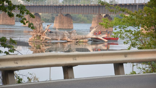 Emergency crews in a rescue boat attempt to talk to a man on a tree in the Missouri River between Broadwater Bay and the Central Avenue West Bridge on Wednesday morning.