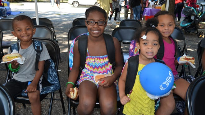Amir Jones, 4, Si'Ani Hutchinson, 9, Jayonna Williams, 3, and Zahmya Williams, 7, all of Millville are sporting their new book bags while eating hot dogs at the third annual No Child Left Behind Fair hosted by Prophetic in Warfare Deliverance and Worship Tabernacle, 1021 Buck St., on Saturday morning.