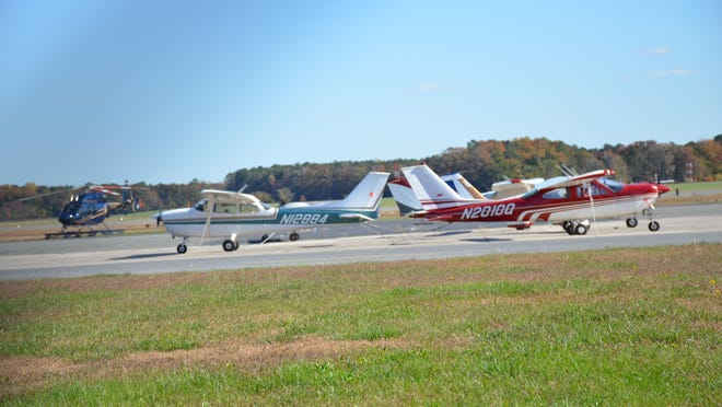 Planes are parked at the Delaware Coastal Airport in Georgetown, including a Delaware State Police helicopter.