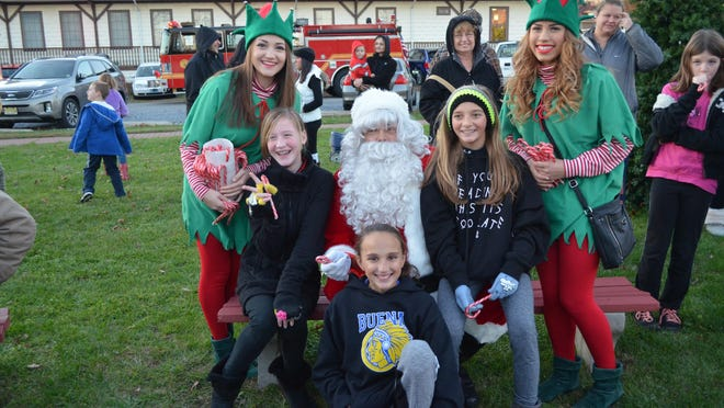 Santa and his elves, Victoria Cox of East Vineland, left, and Clarissa Guzman of Landisville, right, are pictured with Cassidy Gerstle, 11, left, Gianna Scotti, 11, center, and Jessica Perella, 11, all of Buena Vista Township.