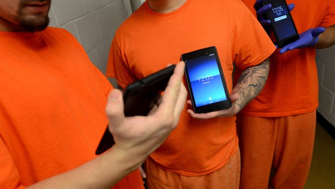 A group of inmates show off their new tablets Monday, Dec. 28, at the Sanilac County jail in Sandusky. Inmates are using these on a free trial basis at the jail.