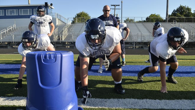 Marysville's offensive line does a drill as Coach Mark Caza watches Wednesday, Aug. 10 at Marysville High School.