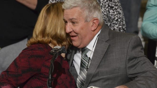 Pennsylvania state Sen. Mike Folmer, R-Lebanon, gets a hug from Lolly Bentch, the Department of Health's patient liaison for the state's medical marijuana program, before he speaks at a Capitol news conference to announce the launch of the program's patient and caregiver registry, Wednesday, Nov. 1, 2017, in Harrisburg, Pa. Folmer was one of the architects of the 2016 law and Bentch helped lobby for it to help her daughter Anna. (AP Photo/Marc Levy)