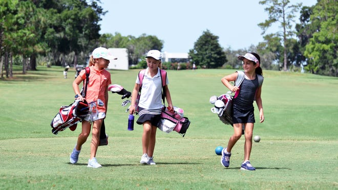 Three Marion County Junior Golf camp attendees take a break between sessions at the Ocala Golf Club.