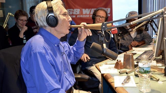"""Arnie """"Woo Woo"""" Ginsburg is seen here blowing his famous horn, with his other cherished noisemakers before him, during WRKO's 50th anniversary celebration in Boston in 2017."""