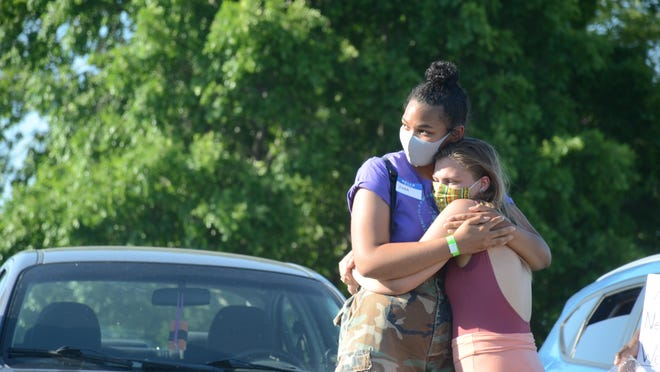 Jeana Lyons, left, receives a hug Friday before telling her story of being pulled over in her own driveway by police, and the fear she suffered because of the color of her skin.