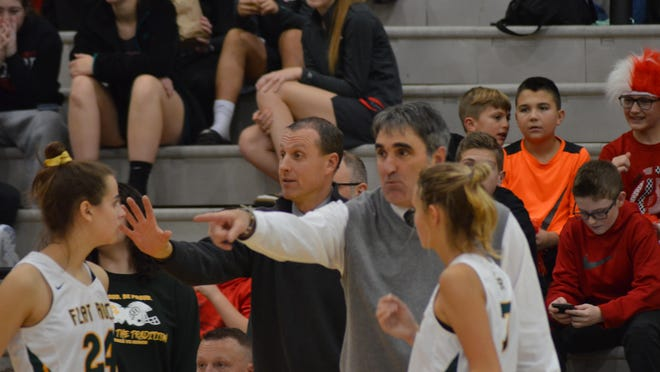 Flat Rock assistant coach Brian Kryk (second from left) and head coach Marc Villemure (second from right) give instructions to Sara Serbantez (24) and Sarah Kopp during a game last season.