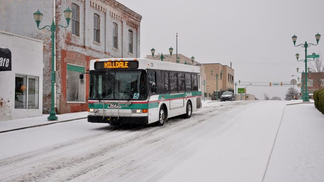 CTS buses make their way down snow-covered streets downtown Monday morning. Many streets were cleared by the afternoon, but more winter weather is coming.