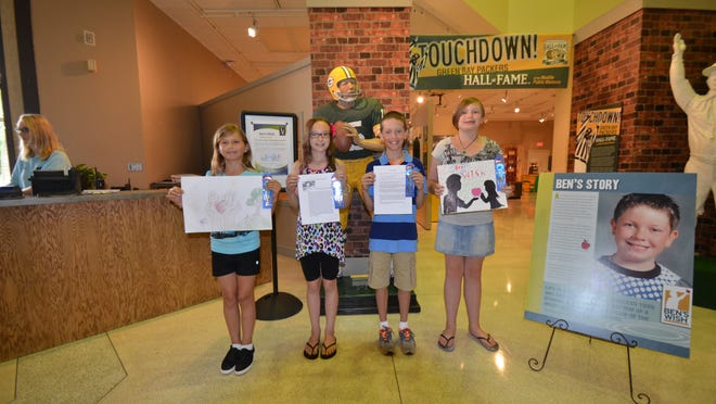 From left, Kathleen Schoneman, Katlin Thompson, Patrick Heil Jr. and Melissa Kerwin share their winning entries at the Neville Public Museum, where they will be on display through Friday.