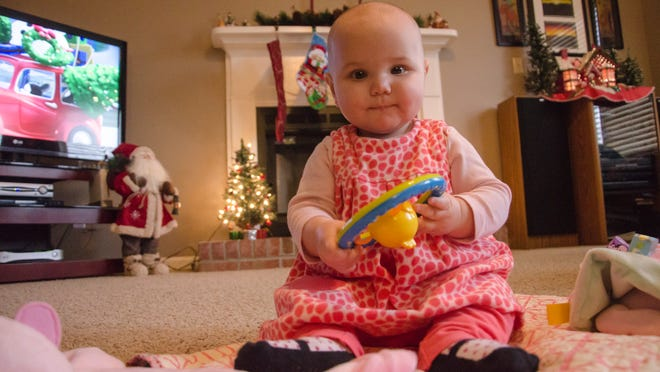 Katelyn Petts plays on the floor of the family's living room Sunday afternoon. Katelyn, who had breathing issues after birth, has become one of several stories highlighted by Riley Children's Hospital for their year-end giving campaign.
