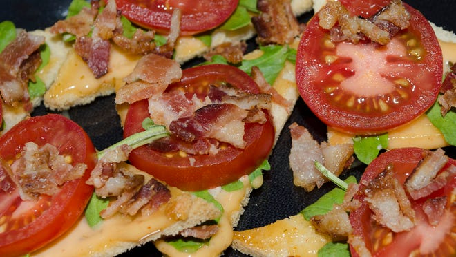A tray of miniature bacon, lettuce, tomato, open-face sandwiches from VKA Kitchen & Catering.