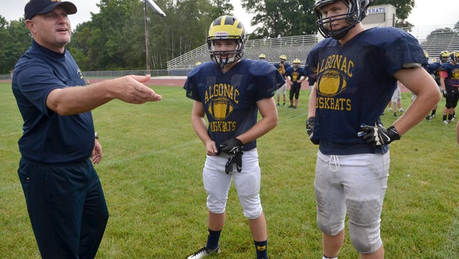 Algonac's coach Scott Barnhart tosses a mobile phone as he does a pre-game coin toss during an inter-squad scrimmage on Aug. 20 during football practice at Algonac High School.