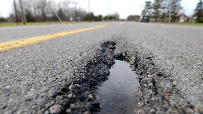 A pothole grows Monday, Dec 1 on Smiths Creek Road west of Richman Road in Kimball Township.