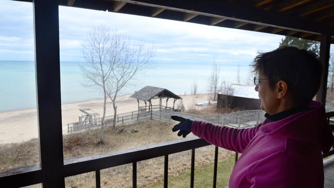 Jill Laidlaw, director of Camp Cavell, points toward the camp's 1,800 feet of waterfront Friday from the balcony of the main lodge at Camp Cavell.