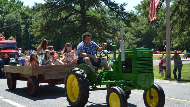 Rudy Cinotti of Richland drives a John Deere tractor and tows his family in a wagon in the 26th annual Buena Vista Independence Day parade.