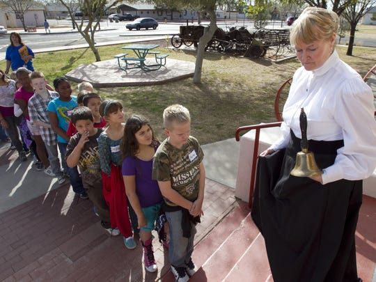 Sharon Eshelman, in a 1912-style dress, walks students into the Peoria Central School Museum. The Peoria Historical Society offers grade-school students the opportunity to feel what school in the early 1900s was like.