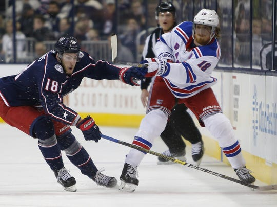 New York Rangers' Marc Staal, right, passes the puck in front of Columbus Blue Jackets' Pierre-Luc Dubois during the first period of an NHL hockey game Sunday, Jan. 13, 2019, in Columbus, Ohio. (AP Photo/Jay LaPrete)