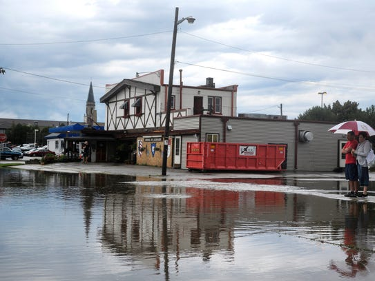 Passerbys look at a flooded intersection in Kenosha,