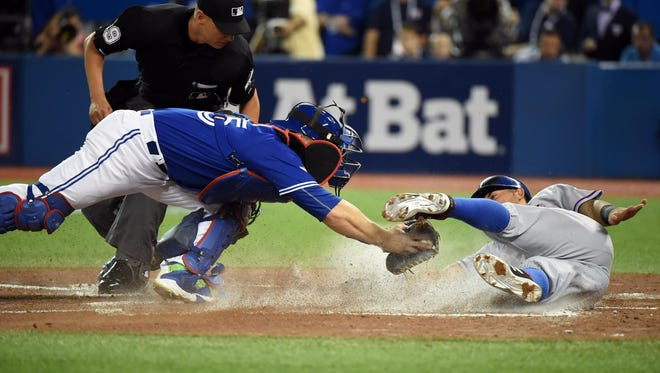 Rangers' Rougned Odor scores a run past the tag of Blue Jays catcher Russell Martin in the second inning.
