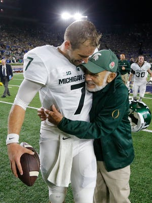 Michigan State quarterback Tyler O'Connor, left, hugs the Rev. Jake Foglio, the team's priest, after MSU's 36-28 win Saturday in South Bend, Ind.
