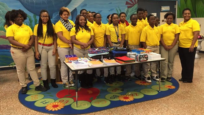 Arthur F. Smith Middle Magnet students pose behind a table of school supplies they helped collect for W.O. Hall Elementary students.