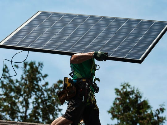 A crew from Solar City installs an array of panels at a home in St. Albans on Thursday, August 11, 2016.
