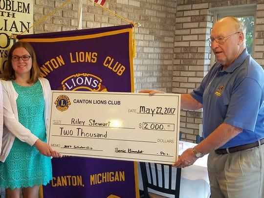 Riley Stewart (left) accepts her scholarship from Canton Lion John Anthony.