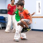 Ajay Lamuth dances during the dinosaur dance Monday night at the Marshall Library during the Jumpin' and Jammin' event.
