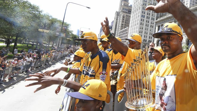 Jackie Robinson West coach Darold Butler, right, and players make their way to Pritzker Pavilion in Chicago during a parade on Aug. 27, 2014.