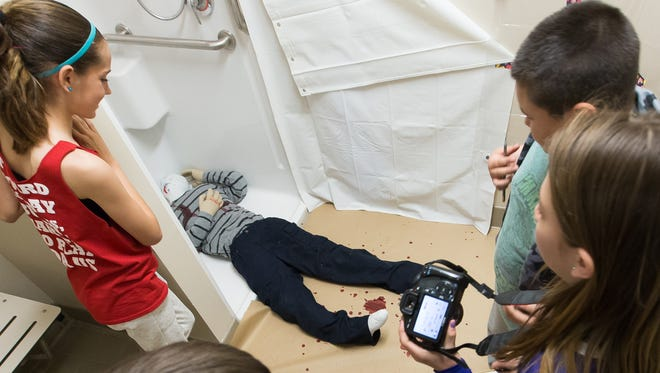 Pictured clockwise from foreground left, Caden Frederich, 12, McKree Riley, 11, Adan Pereyra, 11, and Nova Daniels, 12, look at a mock murder scene on Monday March 20, 2017 during spring break camp at the Museum of Nature & Science.