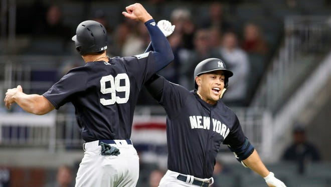 Yankees left fielder Giancarlo Stanton celebrates a home run with right fielder Aaron Judge (99) against the Atlanta Braves in the third inning at SunTrust Park.