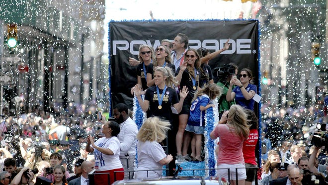 U.S. women's soccer team captain Christie Rampone and her daughters Rylie & Reece share a float with fellow players Abby Wambach, Julie Johnston, Whitney Engen, Christen Press, and NY Governor Andrew Cuomo as they move along Broadway in New York City Friday, July 10, 2015.