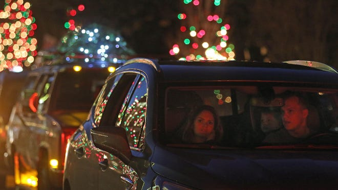 Lines of cars filled with people creep along Main Street as the lights of McAdenville were turned on Tuesday evening, Dec. 1, 2020.