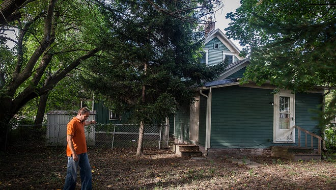 Brad King walks in the large backyard area of an abandoned home along Charles St. in 2017, one of many abandoned properties the city is trying to get a handle on with initiatives like the land bank.