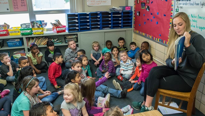 Michigan State University women's crew rower Joanna Beaton reads to students at Riverside Elementary on Tuesday.