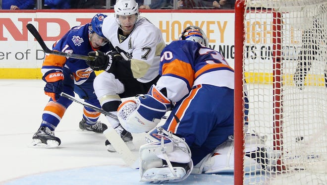 Jean-Francois Berube (#30) of the New York Islanders brushes aside a first period shot by Matt Cullen (#7) of the Pittsburgh Penguins at the Barclays Center on April 2 in the Brooklyn borough of New York City.