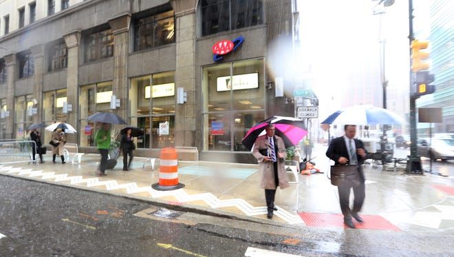 People walked with umbrellas around 11 am Thursday, September 29, 2016 as many were late for work due to heavy rain that snarled roadways all over the metro Detroit area.