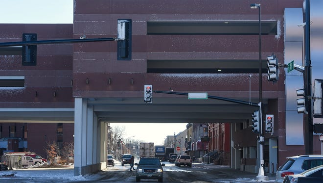 Traffic moves along Fifth Avenue on Monday, Nov. 21, under a portion of the new River's Edge Convention Center parking ramp in St. Cloud.