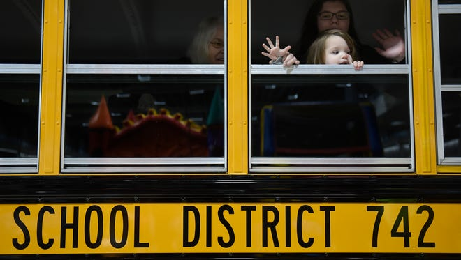 Seen here in this Jan. 7 photo, Maddy Riedman-Lenarz and Emma Krey wave to the crowd while touring a school bus during the District 742 Education Expo at the River's Edge Convention Center in St. Cloud.