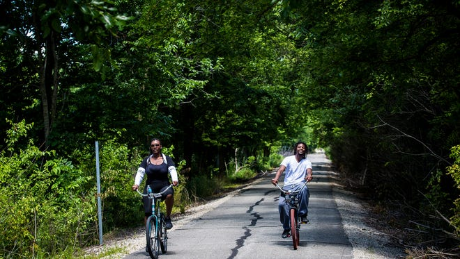 Bikers use the Cardinal Greenway near Mansfield Park Tuesday morning.