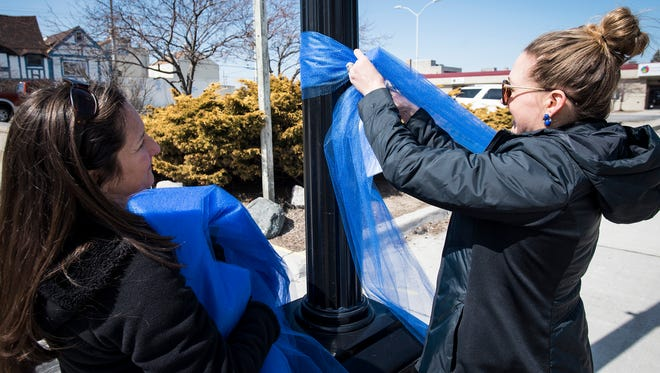 St. Clair County Child Abuse/Neglect Council forensic interviewer Liesl Dobozy, left, and prevention coordinator Lindsay Chopp tie a blue ribbon around a lamp post in downtown Port Huron Monday, April 2. The ribbons are being hung in addition to the pinwheels being planted throughout downtown to raise awareness for child abuse.
