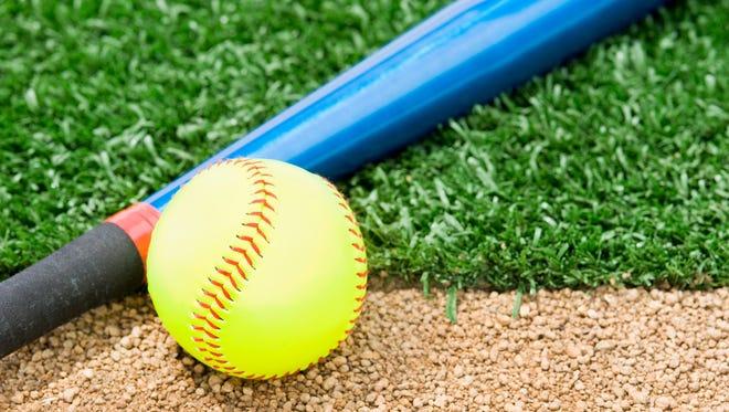 "A New ""Fast Pitch"" Softball and an aluminum bat sitting between the infield grass and dirt of a softball diamond"