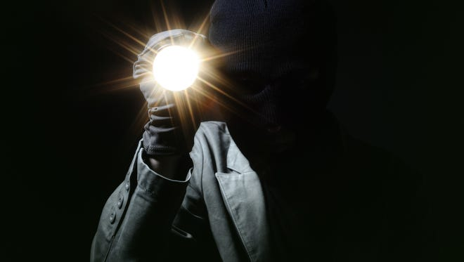 Stock image showing a person with their face covered in the dark.