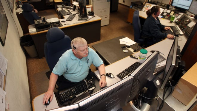 Kenton County consolidated most emergency dispatch services in 2012.  Supervisor Gary Grubbs and dispatcher Julie White are shown in this file photo, which was taken before the dispatch center moved and expanded.