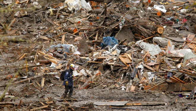 A searcher walks in front of a massive pile of debris at the scene of a deadly mudslide on March 27 in Oso, Wash.