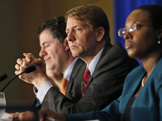 Richard Cordray, center, is director of the Consumer Financial Protection Bureau. It is considering new rules for auto title loans.