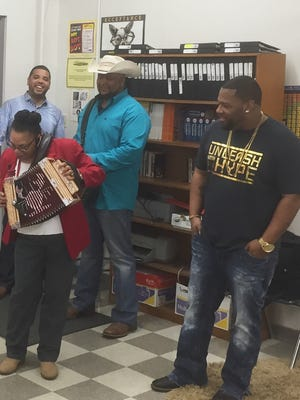 Teacher Ann DeClouette tries her hand at the accordion as, from left, Dustin Cravins, Keith Frank and Chris Ardoin look on Tuesday at N. P. Moss Preparatory School.