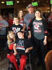 The Stark Family smiles during Saturday's fundraiser. The children are (from left) Madison, Jacob, Kaden and Kylie. with parents Miki and Steve behind.