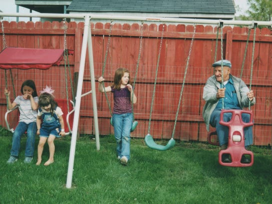 Alexis Riley, Alisandra Torres and Kayla Bishop play on a swing set with Ed Shapley.